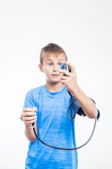 Niño midiendo la presión sanguínea sobre fondo blanco