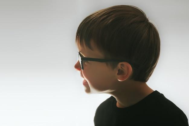 El niño se mira en el espejo en una noche oscura.