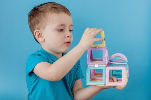 El niño mira a través de la forma en el constructor de color con la conexión de los imanes