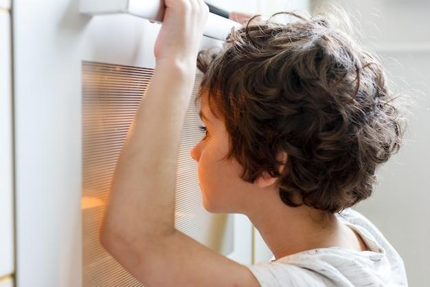 El niño mira por la ventana del horno y espera el almuerzo.
