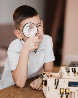 Niño mirando un objeto eléctrico de madera con una lupa