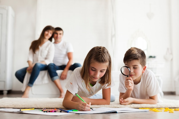 Niño mirando a través de la lupa durante su dibujo de la hermana en el libro frente a sus padres sentados sobre la cama