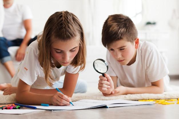 Niño mirando a través de la lupa durante su hermana dibujo en el libro