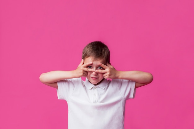 Niño mirando a través de v firmar sobre fondo rosa