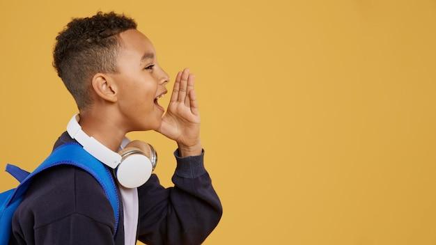 Niño con mochila azul gritando espacio de copia