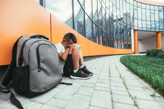 Niño con mochila en depresión sentado en el suelo no quiere volver a la escuela