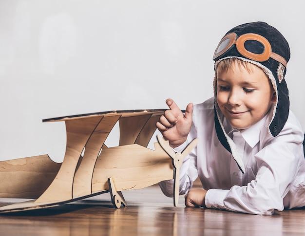 Niño con modelo de avión de madera y gorra con gorra