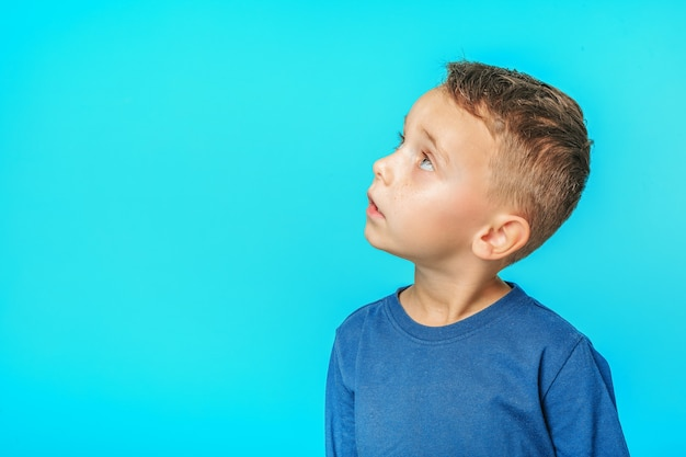 Un niño modelo posando sobre fondo turquesa