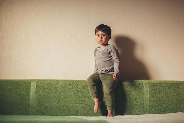 Niño molesto sentado en el sofá cerca de la pared y mirando triste a la cámara durante el encierro