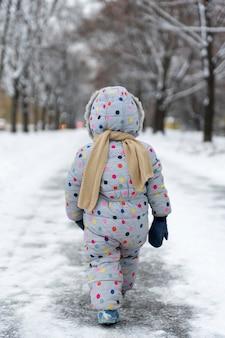 Niño con mono y bufanda está caminando en el parque cubierto de nieve. vista trasera. marco vertical.