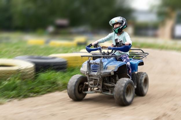 Un niño monta un atv en la pista.