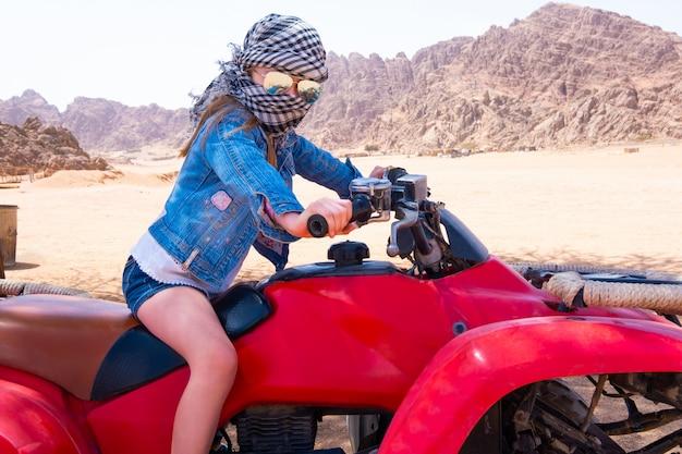 Niño montando en quad en el desierto