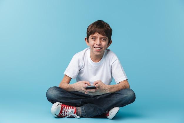 De niño morena europeo con pecas vistiendo camiseta blanca casual sosteniendo y usando el teléfono inteligente mientras está sentado en el piso aislado sobre la pared azul