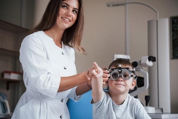 Niño mostrando algo con su dedo índice. niño sentado en el gabinete del médico y haber probado su agudeza visual.