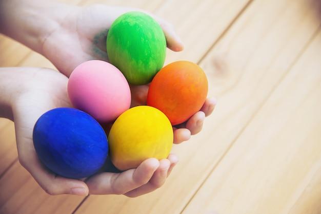 Niño mostrando huevos de pascua coloridos felizmente - concepto de celebración de vacaciones de semana santa