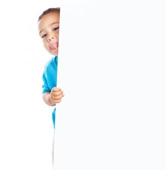 Niño mostrando la lengua y sujetando un cartel en blanco