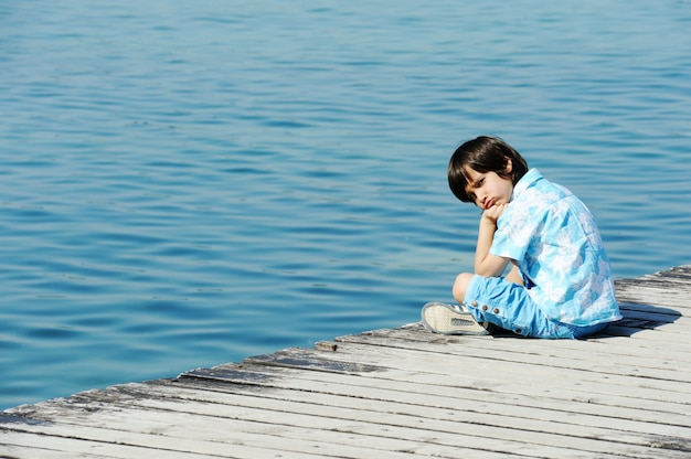 Niño por muelle de madera en un hermoso mar
