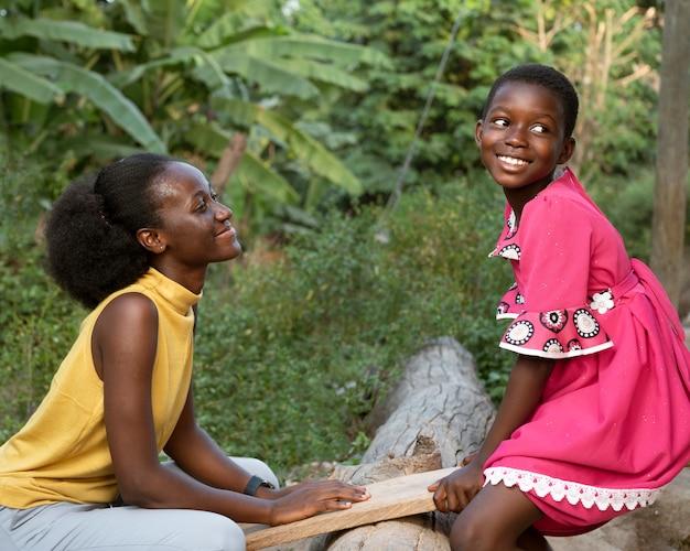 Niño y mujer africana de tiro medio