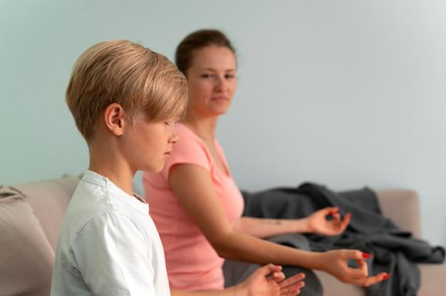 Niño y mujer meditando plano medio