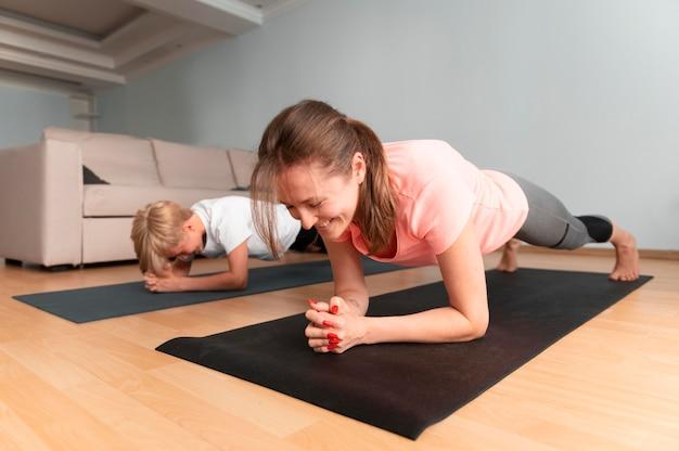 Niño y mujer de tiro completo con colchonetas de yoga