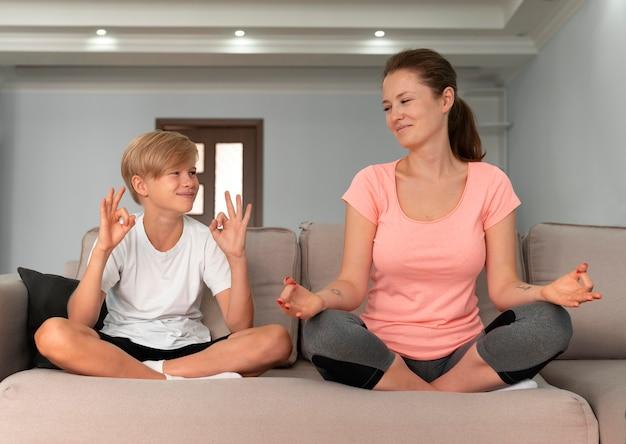 Niño y mujer de tiro completo meditando
