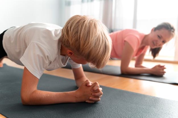 Niño y mujer de tiro medio con colchonetas de yoga