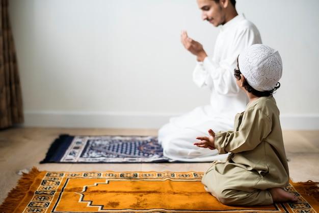 Niño musulmán aprendiendo a hacer dua a alá.