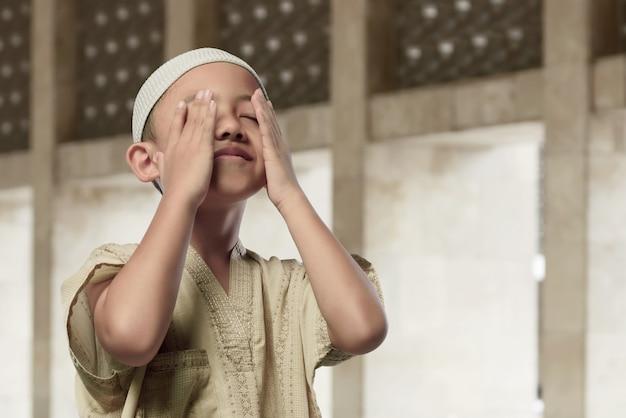 Niño musulmán asiático alegre rezando a dios
