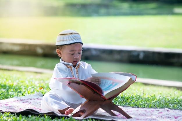 Un niño musulmán asiático está leyendo el corán en el parque, concepto del islam,