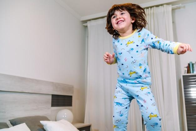 Niño muy feliz saltando en la cama con pijama antes de irse a la cama