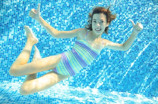 El niño nada bajo el agua en la piscina, la niña adolescente activa y feliz se zambulle y se divierte bajo el agua, se ejercita y se divierte en vacaciones familiares en el resort