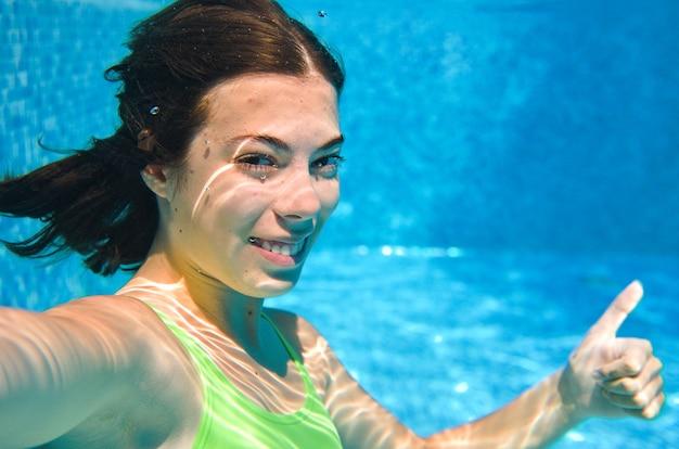 El niño nada bajo el agua en la piscina, la niña adolescente activa feliz se zambulle y se divierte bajo el agua