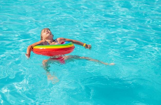 El niño nada y se zambulle en la piscina. enfoque selectivo.