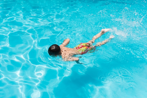 Niño nadando en la piscina