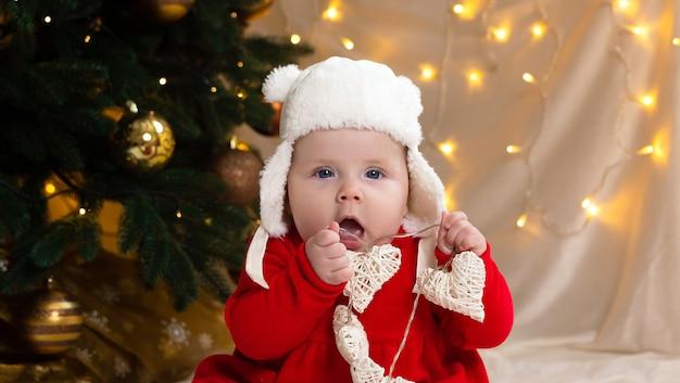 Niño de navidad mirando a la cámara y sosteniendo una guirnalda con corazones.