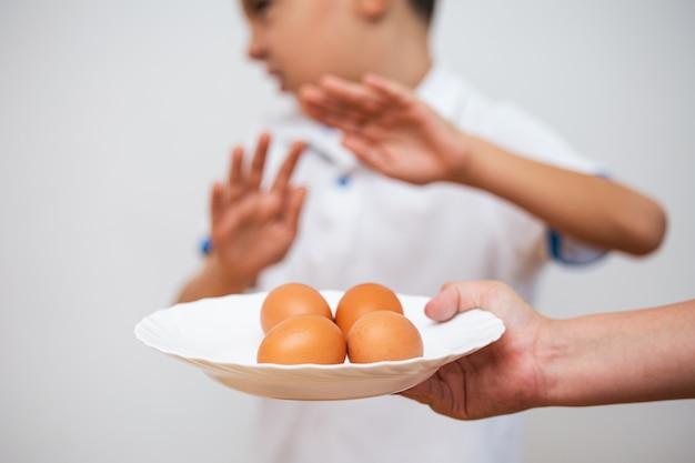 Niño negándose a comer huevos. restricción prohibida para las alergias afectadas sin huevo.