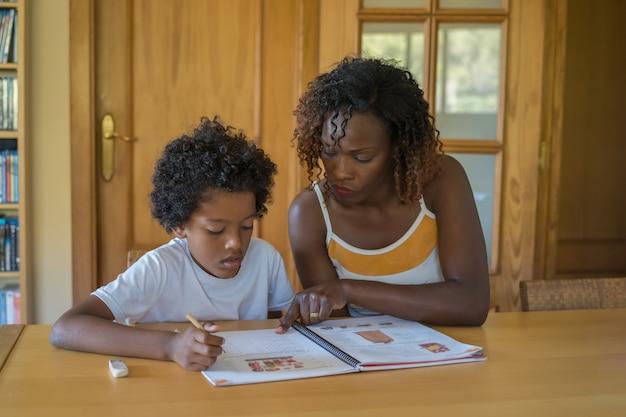 El niño negro hace la tarea en casa con la atención de su madre. de vuelta a la escuela