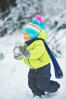 El niño en la nieve en el parque. un niño juega en winter park. adorable niño caminando en el bosque de invierno de nieve