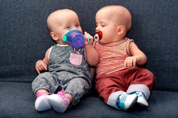 Niño y niña hasta el año beben agua de una botella en el sofá. el concepto de gemelos en la familia.