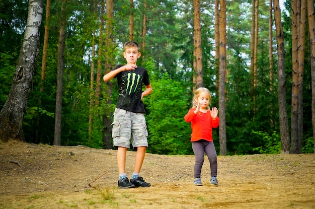 Un niño y una niña bailan alegremente en un claro del bosque.