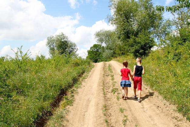 Un niño y una niña caminan por un camino de tierra en un día soleado de verano. niños tomados de la mano juntos mientras disfruta de la actividad al aire libre.