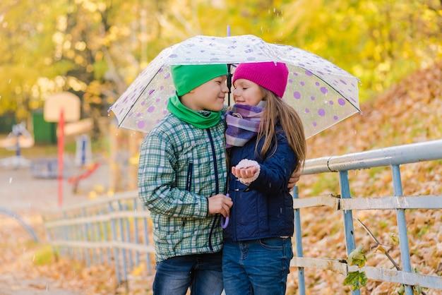 Niño y niña caminan en el parque otoño húmedo y abrazan