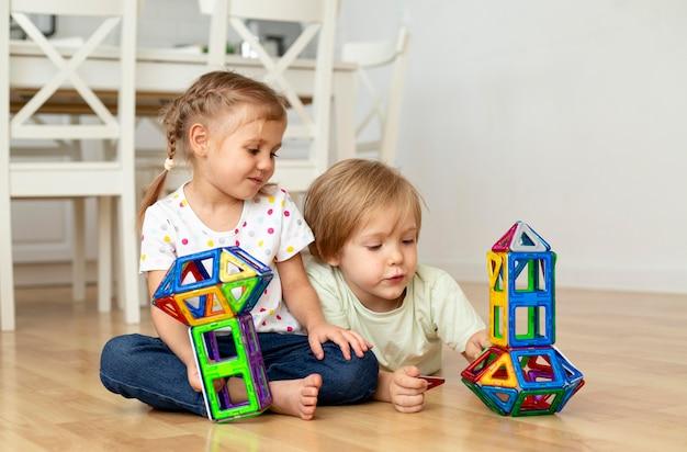 Niño y niña en casa jugando con juguetes juntos