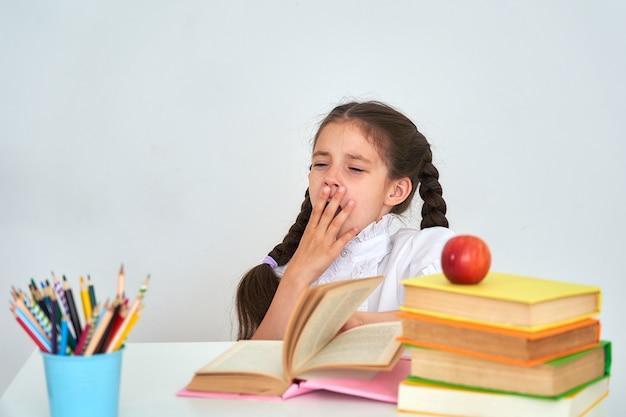 Niño niña colegiala sentada en un escritorio y bostezando. escuela cansada y tarea.