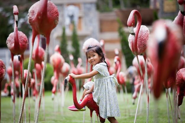 Niño niña divirtiéndose en el parque de la estatua de flamenco