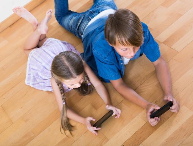 Niño y niña enterrando en teléfonos móviles