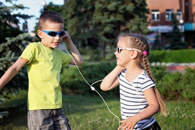 Niño y niña escuchando música con auriculares y bailando