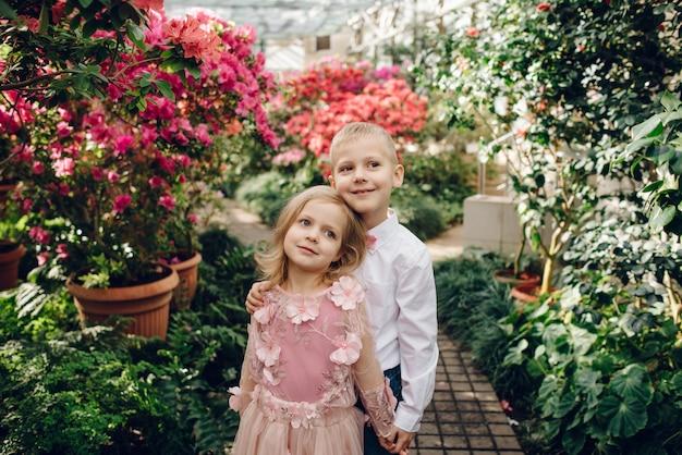 Niño y niña están caminando en un jardín floreciente
