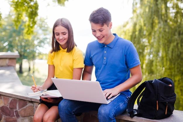 Niño con niña estudiando en la naturaleza