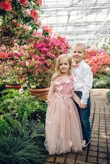 Niño y niña felices están caminando abrazándose en el jardín floreciente de primavera